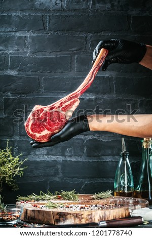 Male hands of butcher or cook holding tomahawk beef steak on dark rustic kitchen table background