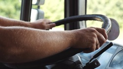 Male hands of lorry driver holds a big steering wheel while driving a truck at summer day. Trucker riding to destination at country road. Concept of logistics and transportation. Close up Slow mo.