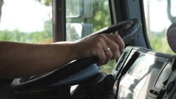 Male hands of lorry driver holds a big steering wheel while riding a truck through countryside. Trucker driving to destination at country road. Logistics and transportation concept. Slow motion.