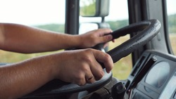 Male hands of trucker holds a big steering wheel while operating a truck through countryside. Lorry driver riding to destination at country road. Concept of logistics and transportation. Close up.