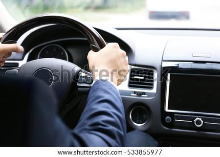 Male hands on steering wheel, closeup