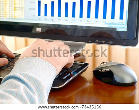 Male hands on the keyboard in front of computer screen with charts