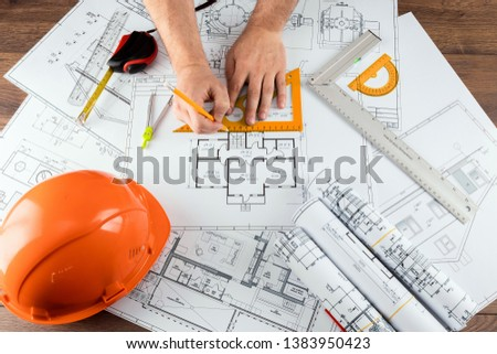 Male hands, Orange helmet, pencil, architectural construction drawings, tape measure. The architect designs the building. The concept of architecture, construction, engineering, design. Copy space.