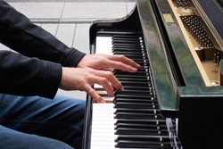 Male hands playing a piano