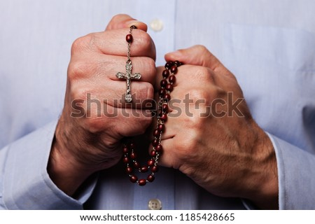 Male hands praying holding a beads rosary with Jesus Christ in the cross or Crucifix on black background. Mature man with Christian Catholic religious faith #1185428665