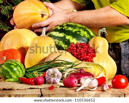 Male hands preparing vegetable on wooden boards.