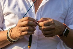 Male hands put bait on a fishing rod's hook. Fishing with a spinning rod