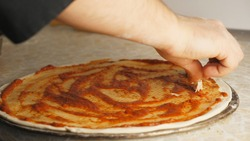 Male hands putting pieces of boiled chicken on the dough in metal form at kitchen. Arms of cook adding ingredient on pastry for preparing tasty pizza at restaurant. Concept of cooking food. Close up