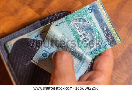 Male hands shows 50 Ringgit Malaysia in leather wallet on a wooden table. RM50 in mans hand. Malaysian Ringgit shown by young man in a wallet. Close up to Malaysian currency. Hands flip through money