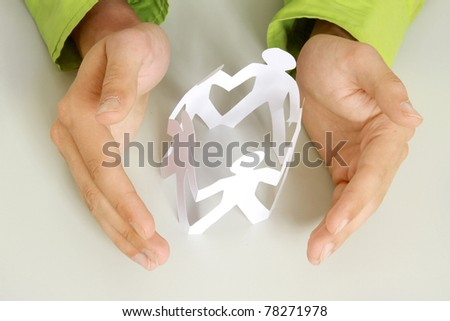 Male hands taking care of paper people