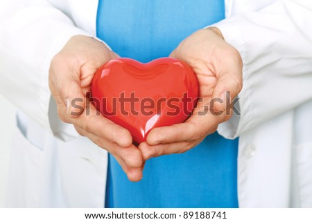 Male hands taking care of red heart symbol