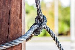 Male hands tie a rope tree,Rope knot line tied together with nature background,as a symbol for trust, teamwork or collaboration.