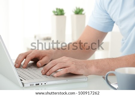 Male hands typing on laptop computer keyboard, closeup portrait.