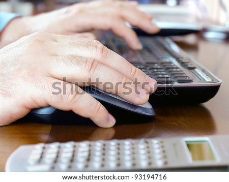 Male hands using a computer mouse and keyboard