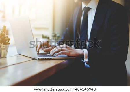 Male hands using laptop in modern coffee shop or loft, professional businessman in black suit working on new project with notebook computer while sitting at his office, flare light, blurred background