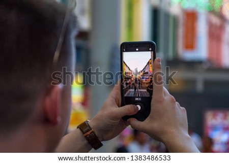 Male hands using smartphone taking a photo on the street at dusk.