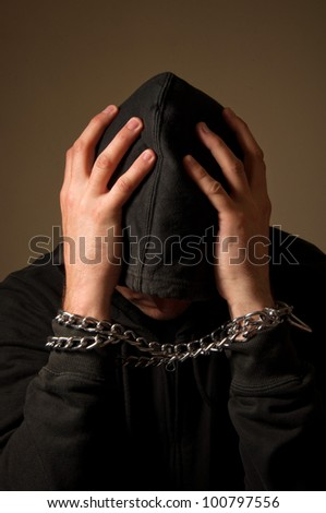 Male hands with chain wrapped around them, prisoner concept