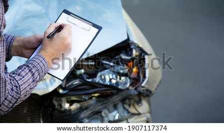 Male hands with paper mock up auto insurance blank against Destroyed car in crash traffic accident. Smashed broken front auto headlight. Auto life and health insurance. Long web banner