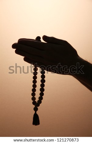 male hands with rosary, on brown background