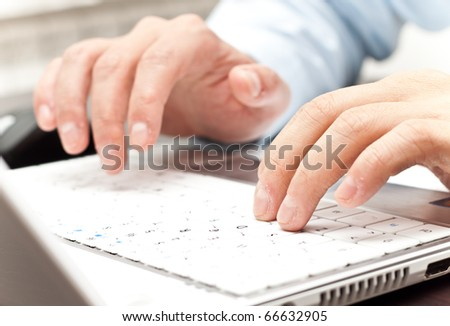 male hands writing on a white laptop