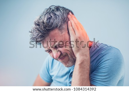 male having ear pain touching his painful head isolated on gray background Foto stock ©