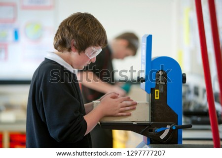 Male high school student in safety goggles using machinery in woodwork