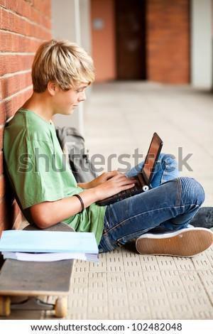 male high school student using laptop in school