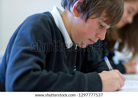 Male high school student working at desk in classroom