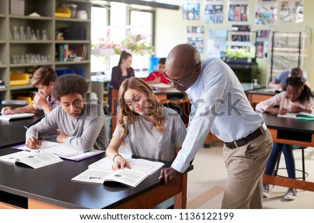 Male High School Tutor Teaching Students In Biology Class