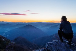 Male hiker crouching on top of the hill and enjoying scenic view of twilight landscape below. Hiking, achievement, expectation, optimism and self-reflection concepts.