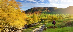 Male hiker exploring the Great Langdale valley in the Lake District, famous for its glacial ribbon lakes and rugged mountains. Popular vacation destination in Cumbria, North West England.