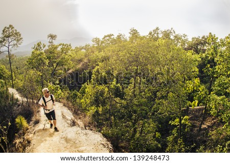 Male hiker in white shirt and backpack walking along narrow mountain path in red canyon