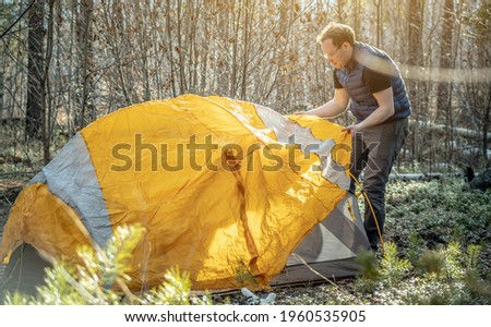 Male hiker is setting up a bright orange tent in the forest. Concept of tourism, hiking and staying in nature. Stockfoto ©