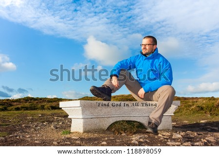 Male hiker sitting on a bench with slogan find god in all things and looking towards the light