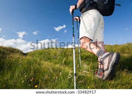 Male hiker walking along a mountain path. Horizontal orientation. Low angle view