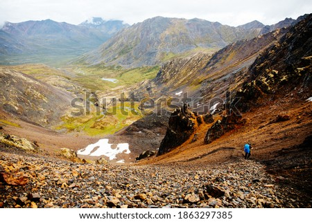 Male hiker walks in Tombstone Territorial Park, Yukon Canada. Huge stunning mountains and a lake is in the distance. Inspiring landscape. Summer and Fall hiking. Campground with tents. Stock photo ©