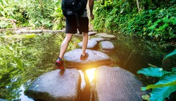 Male hiker with backpack crossing a river on stones.