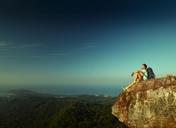 Male hiker with backpack relaxing on top of a mountain