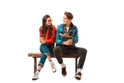 male hipster with paper cup of coffee pointing to girlfriend sitting on bench isolated on white