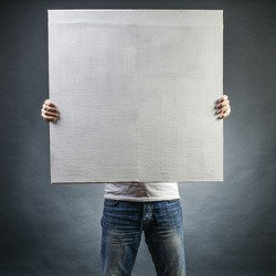 male holds a square canvas primed