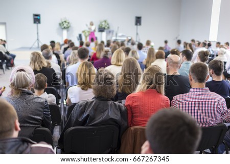 Male Host Speaking on Stage in Front of Group of Professionals During a Conference.Horizontal Image Orientation