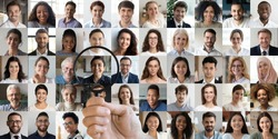 Male hr manager holding magnifying glass head hunting choosing finding new unique talent indian female candidate recruit among multiethnic professional people faces collage. Human resources concept.