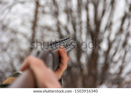 Male hunter aims a hunter rifle. Winter hunting.