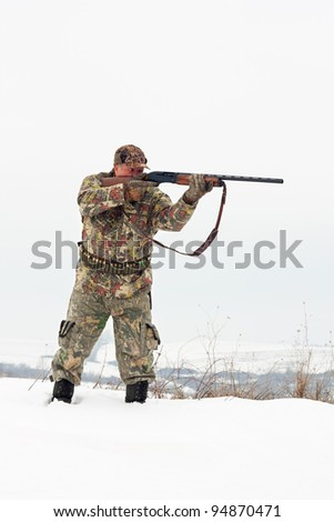 Male hunter in camouflage aiming at his target or prey with his gun.Winter scene
