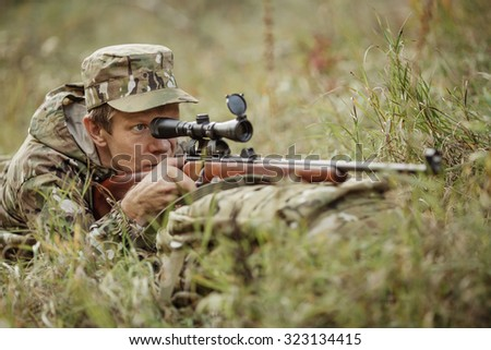 Male hunter in camouflage clothes ready to hunt with hunting rifle