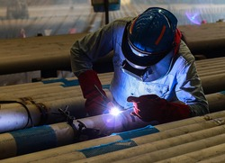 Male in face mask welds with argon-arc welding