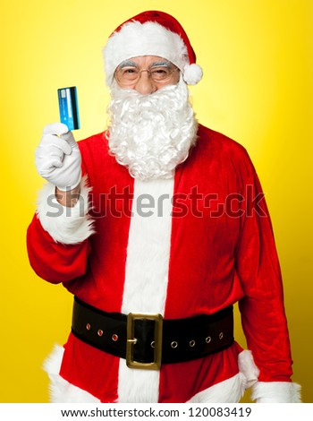 Male in Santa costume posing with his cash card. Lets go shopping. - stock photo