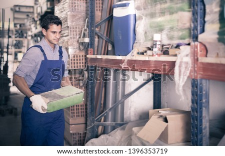 male in uniform is choosing cement in the building store room