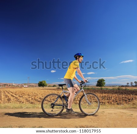 Male in yellow shirt riding a bike outdoor, Macedonia