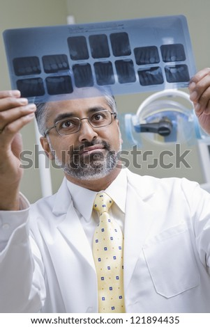Male indian dentist examining x-ray report in clinic